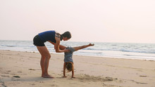Young Sporty Mother Train Little Girl Doing Handstand Position.  Mom With Little Daughter Doing Gymnastic On The Beach. Acrobatic Exercise Outdoor.