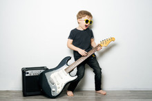 Children's Hobbies: A Little Boy In Black Glasses Plays The Electric Guitar, Imitates A Rock Star.