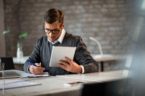 Fotografía  Businessman writing financial reports and using digital tablet in the office