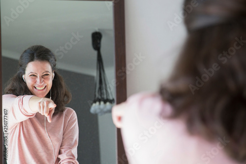 Obraz Excited young woman dancing in front of mirror - fototapety do salonu