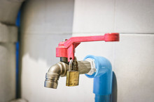 Tap With Drinking Water, The Red Valve Is Closed On The Padlock. Water Consumption Concept