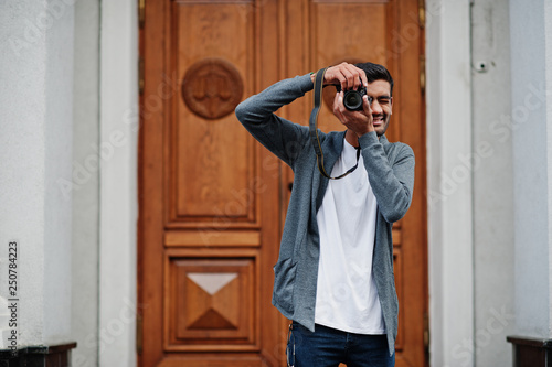 Photo Stylish indian young man photographer wear casual posed outdoor with dslr photo camera at hands