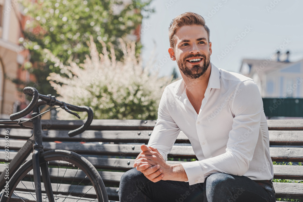 Fototapety, obrazy: Ready to go. Young smiling man sitting on a bench in the park with a bicycle beside him. Rest and relax concept