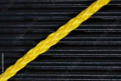 Fényképezés closeup photo of yellow plastic cord on black background