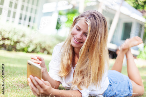 Valokuva  Beautiful blonde girl, on a summer green lawn, with a smartphone in her hands en
