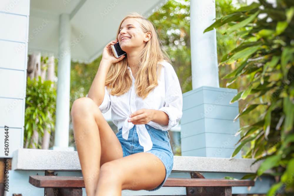 Valokuva  Beautiful blonde girl, on the summer terrace of her house, with a smartphone in