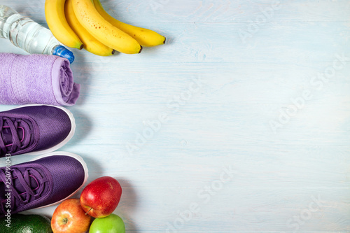 Carta da parati Sport shoes, bottle of water, fruits and towel on blue wooden background