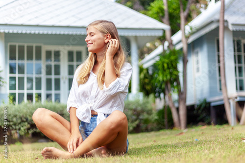 Valokuvatapetti Beautiful young blonde woman at summer green lawn, enjoys the sun spring and summer