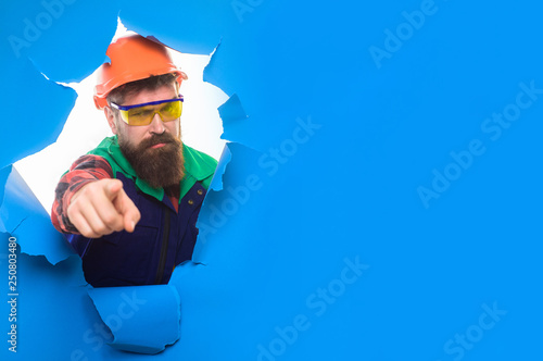 Builder in hard hat shows finger on you. Mechanical worker points forward. Construction worker in hardhat&protective glasses. Bearded man in construction helmet through hole in paper pointing at you.