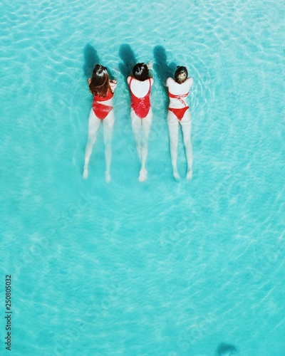 Photo Aerial photo of three baywatch girls in red swimsuits are relaxing on the beach, in azure light-blue sea, in Krabi, Phuket, Thailand