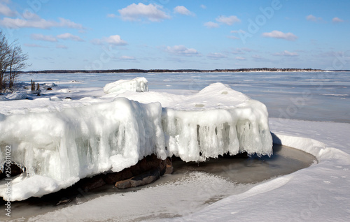 Fotografija .Ice floe with icicles on the shore of Lake Ladoga on the edge of the forest