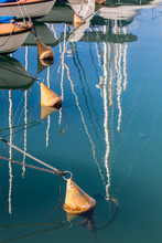 Old Yellow Buoys Tied To Boats
