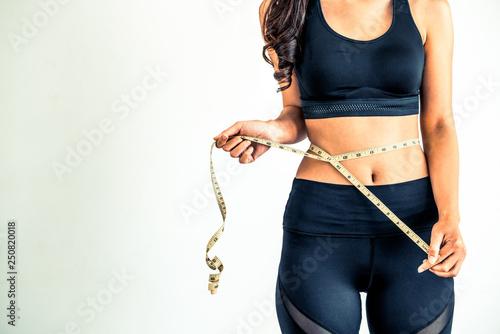Obraz Close up shot woman with slim body measuring torso - fototapety do salonu