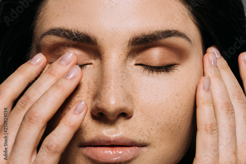 Fototapeta close up view of tender girl with freckles on face touching closed eyes obraz
