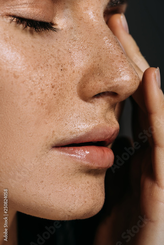 close up view of tender woman with freckles on face isolated on grey - fototapety na wymiar
