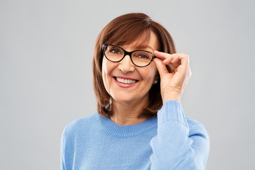 Fototapetavision and old people concept - portrait of smiling senior woman in glasses over grey background