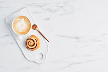 Freshly Baked Cinnamon Bun With Spices And Cocoa Filling And Coffee Or Cappuccino With Latte Art On White Serving Plate Over White Marble Background. Top View. Copy Space For Text. Swedish Breakfast.