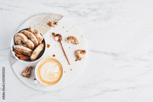 Fototapeta Coffee or cappuccino with latte art and gingerbread biscuits on white marble serving plate over marble background. Breakfast concept. Top view with copy space for text. obraz