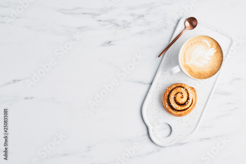 Obraz na płótnie Freshly baked cinnamon roll with spices and cocoa filling and coffee or cappuccino with latte art on white serving plate over white marble background