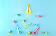 Different Colorful Paper Airplanes And Crumpled Paper Balls On Blue Gradient Background. Creativity Concept. Close Up, Copy Space, Top View, Flat Lay.