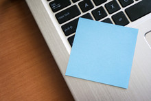 Style Image Of Modern Laptop Computer Keyboard. Blue Sticky Note  To The Computer On A Brown Wooden Desk