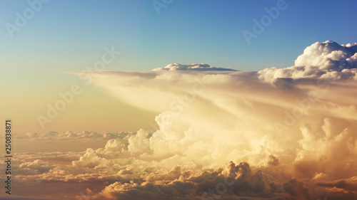 flying through picturesque evening clouds softly lit by the sun with pale blue sky on the background beautiful peach orange dramatic cloudscape on sunset view from above buy this stock photo and adobe stock