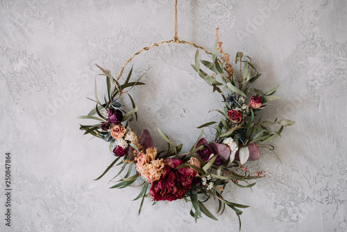 Beautiful hand made everlasting dry wreath made of roses, hydrangea flowers and eucalyptus on the grey wall background - 250847864