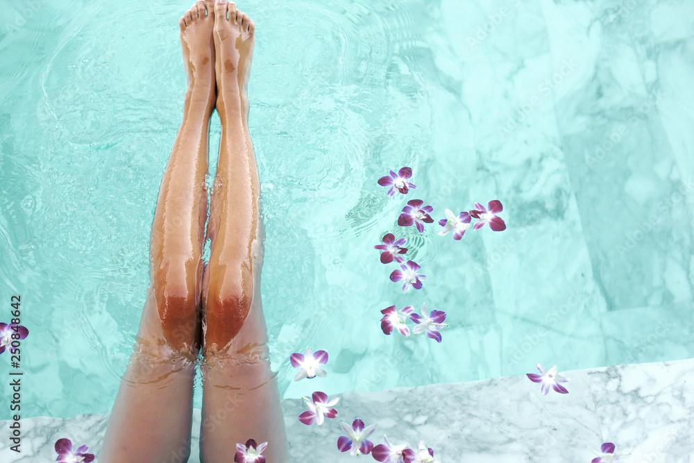 Fototapeta Girl relaxing in tropical spa pool with flowers