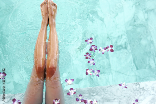 Fotografie, Obraz  Girl relaxing in tropical spa pool with flowers