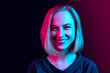 Happy business woman standing and smiling on neon studio background. Beautiful female half-length portrait. Young emotional woman. The human emotions, facial expression concept