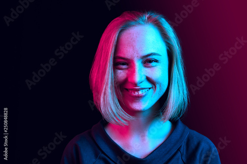 Obraz na plátne Happy business woman standing and smiling on neon studio background