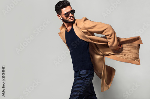 Elegant young handsome main coat wearing glasses. Studio fashion portrait.