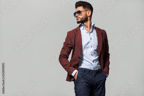 Elegant young handsome man in suite wearing glasses. Studio fashion portrait. - fototapety na wymiar