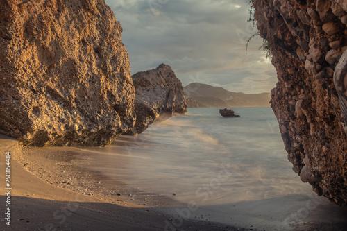 Poster Marron chocolat Nerja, Malaga, Andalusi, Spain - January 20, 2019: Sunrise among cliff rocks in the village of Nerja, southern Spain