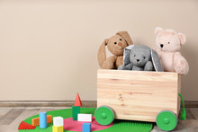 Wooden Cart With Stuffed Toys And Constructor On Floor Against Light Wall. Space For Text