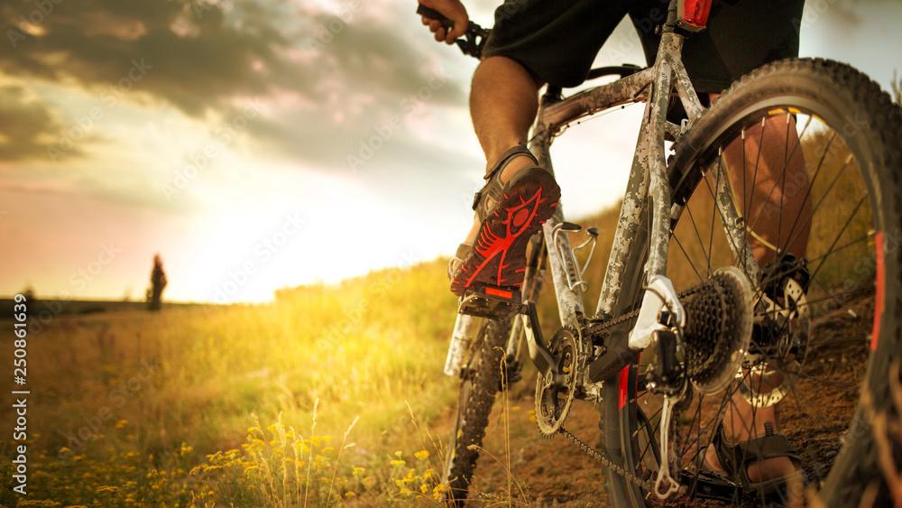 Fototapeta Cyclist riding bike down hill at sunset