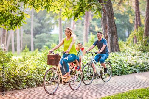 Fotografia Happy family is riding bikes outdoors .