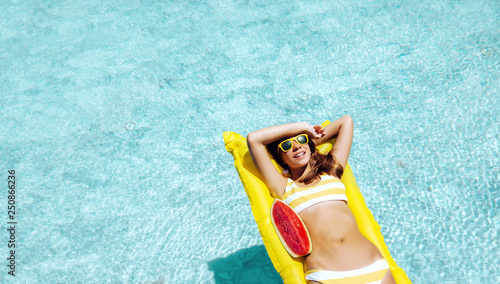 Deurstickers Ontspanning Girl floating on beach mattress and eating watermelon in the hotel pool