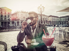 Handsome Young Man Drinking Espresso Coffee, Wearing Elegant Coat Posing At Table Outside On Urban Background.