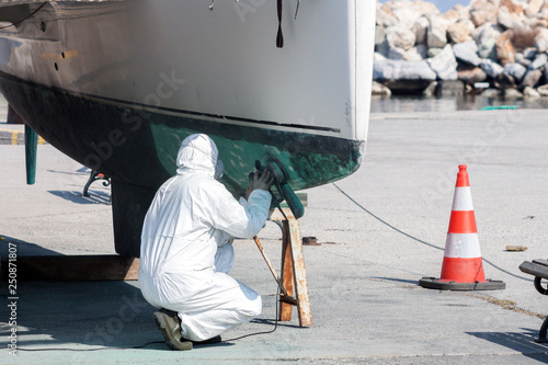 Foto Worker wearing protection suit and mask is sanding down old paint from catamaran