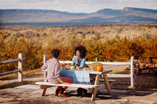 Couple Sitting At Picnic Table...