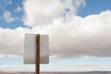 Back Of Road Sign Against Blue Sky And Clouds