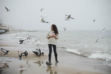 Young Curly Woman Feeding The Birds On The Sea Beach On Foggy Day