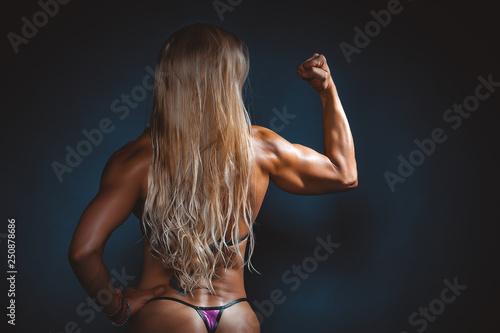 Obraz na płótnie very muscular handsome athletic woman on black background
