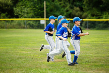 Young Baseball Players Running