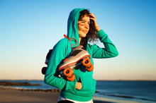 Woman With  Roller Skates Standing On Beach