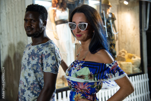 Spoed Foto op Canvas Carnaval Portrait of happy interracial amorous couple. African man looking at his Caucasian woman. Elegant young couple while strolling through the city. The girl wears sunglasses and puts a hand on the boy's
