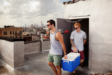 Two Male Friends Carrying Cooler Out To City Roof