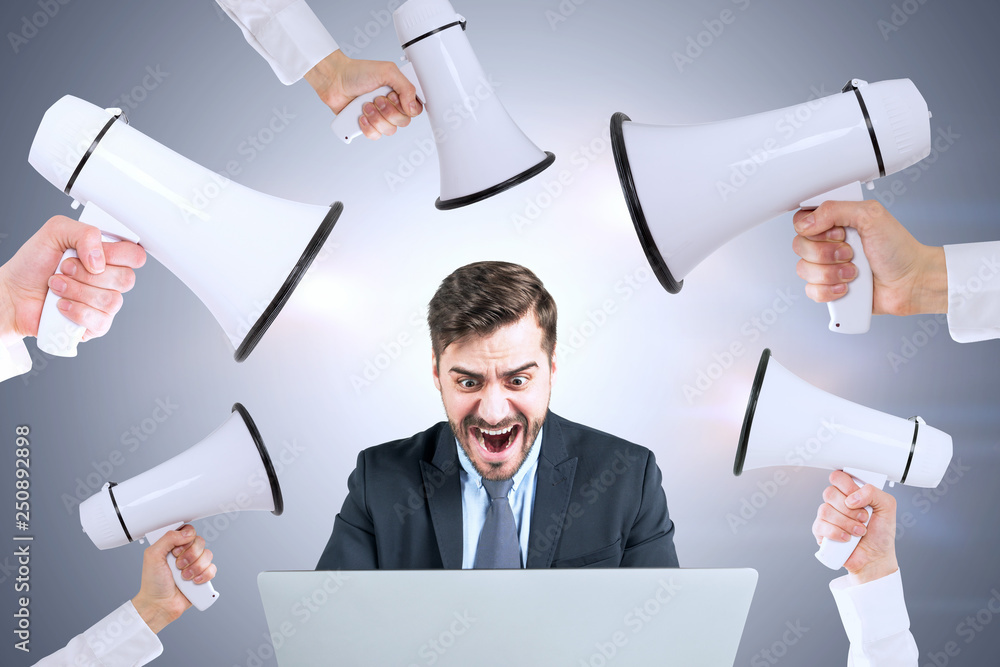 Fototapeta Stressed man with laptop, hands with megaphones