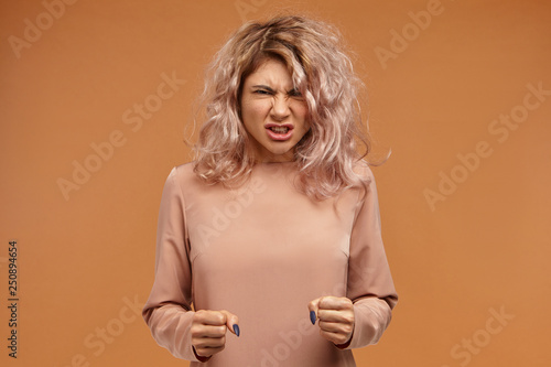 Fotografiet Enraged furious young woman with voluminous hair clenching fists and roaring, expressing her anger, being mad at neighbors who make noise